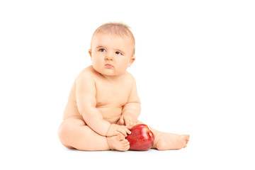Studio shot of a baby playing with an apple