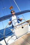 Skipper on sailboat navigating in mediterranean sea
