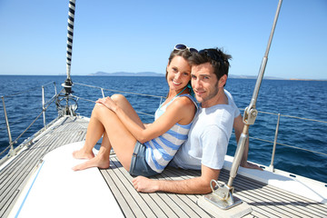 Happy couple navigating on sailboat