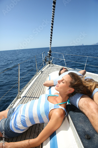 Couple taking sun on sailboat