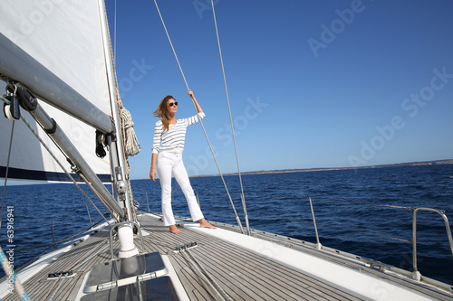 Attractive woman standing on sailboat deck