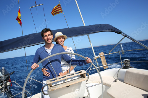 Happy couple enjoying journey on sailboat