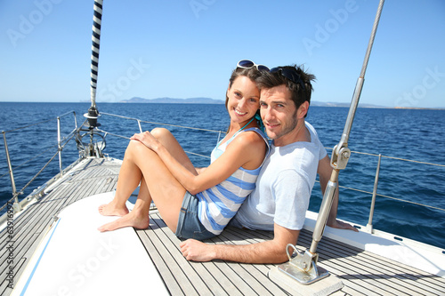 canvas print picture Happy couple navigating on sailboat