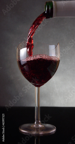 Pouring red vine into a broken glass
