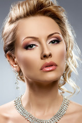Portrait of young beautiful woman with jewelry. Beauty photo