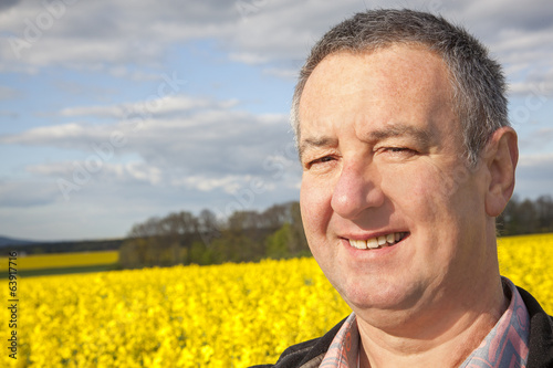 Farmer stands in rape field