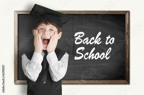 Cheerful little boy on blackboard. Looking at camera