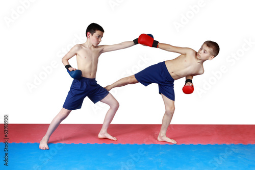 Two athletes are training in shorts kick low kick on the mat