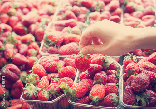 human hand picks up strawberries on market, intagram effect