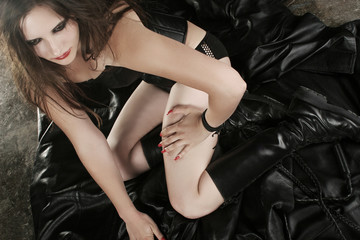 Attractive woman in leadher on the floor.