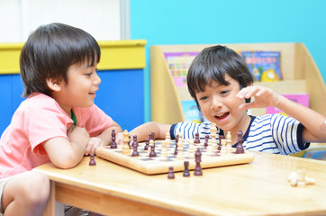Little siblibg boy playing chess