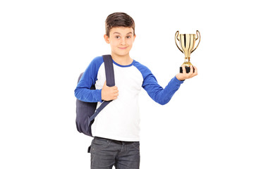 Boy with backpack holding a trophy