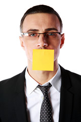 Portrait of businessman with mouth covered with a paper card