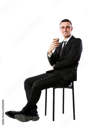 Cheerful businessman sitting with cup of coffee