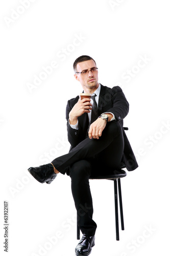 Pensive businessman sitting with cup of coffee