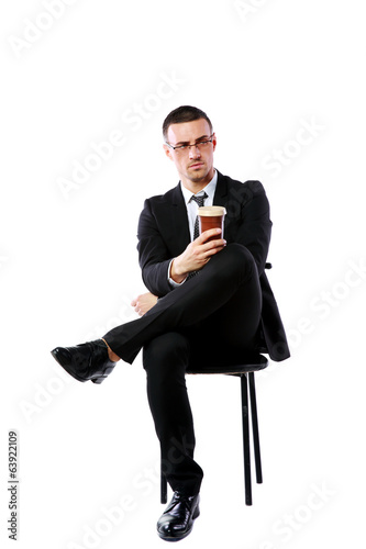 Confident businessman sitting with cup of coffee