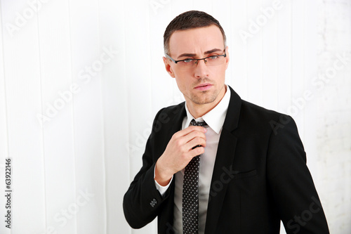 Handsome businessman in glasses adjusting his tie