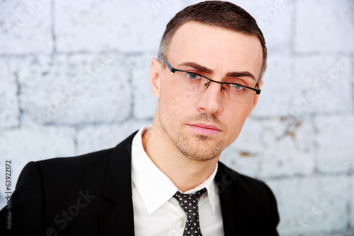 Handsome businessman standing near brick wall