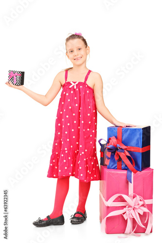 Little girl standing by a stack of presents
