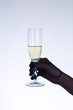 Female hand in black opera glove holding champagne glass