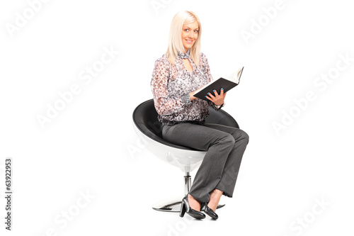 Woman holding book seated on a modern chair