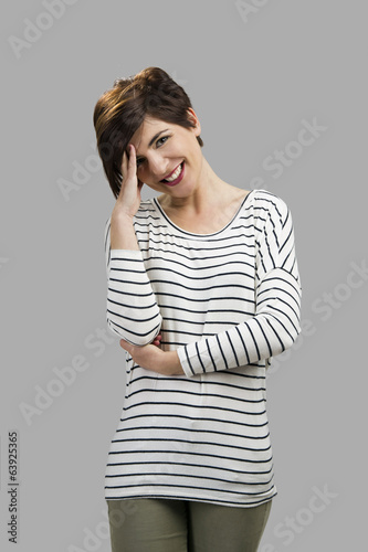 canvas print picture Portrait of a beautiful woman smiling, over a gray background