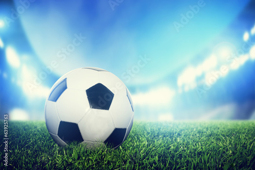 canvas print picture Football, soccer match. A leather ball on grass on the stadium
