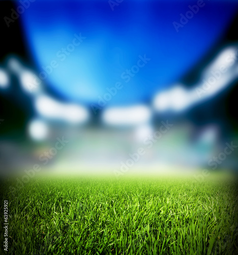 Football, soccer match. Grass close up, lights on the stadium.