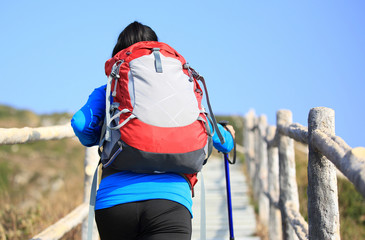 young woman hiker climbing stone stairs to mountain peak
