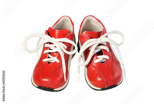 Pair of children's shoes on the red cord on  white