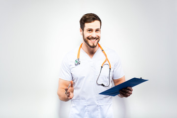 Handsome doctor standing next to wall