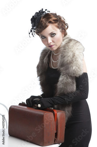 Woman in black dress with suitcase