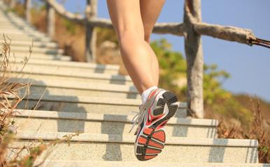 woman runner athlete feet running on mountain stairs