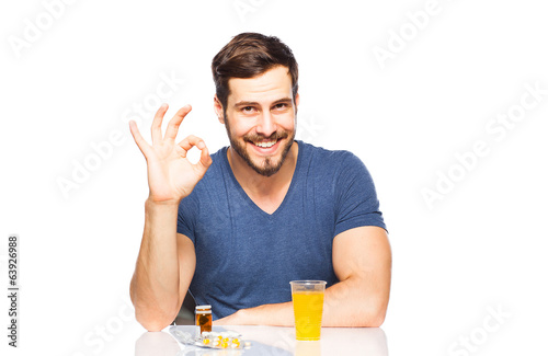 Man having in front pills and orange juice