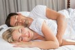 Relaxed couple lying in bed with eyes closed