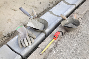 Curb stone, mason tools trowel gloves meter at construction site