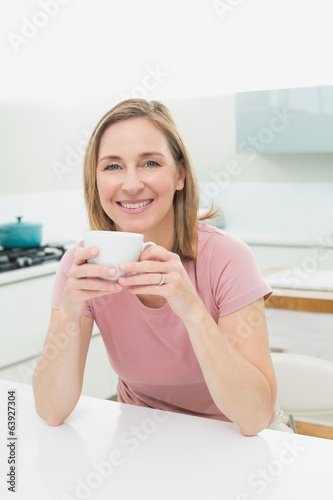 Relaxed smiling woman having coffee in kitchen