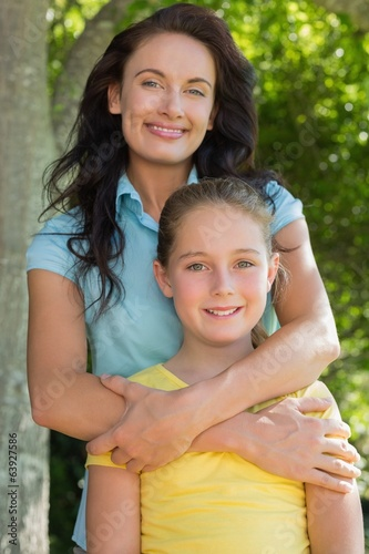 Mother and daughter standing in park