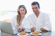Couple using laptop on breakfast table