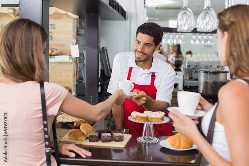 Friends with male barista at counter in coffee shop