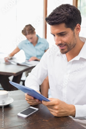 Happy man using digital tablet in coffee shop