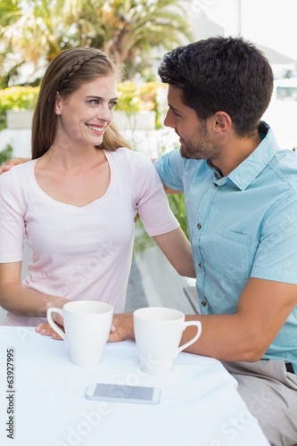 Smiling couple with coffee cups at café