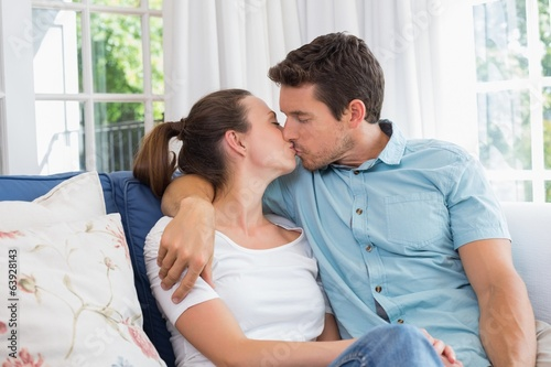 Loving couple kissing in living room