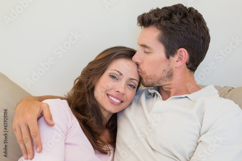 Loving young couple sitting on couch