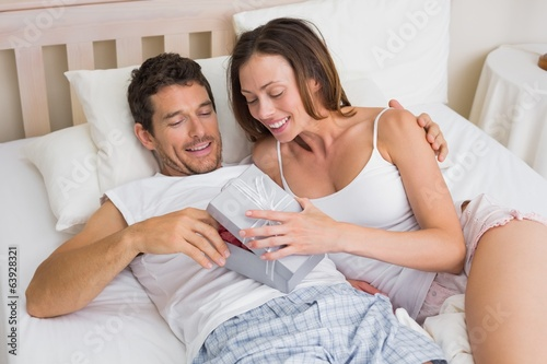 Couple with gift box lying together in bed