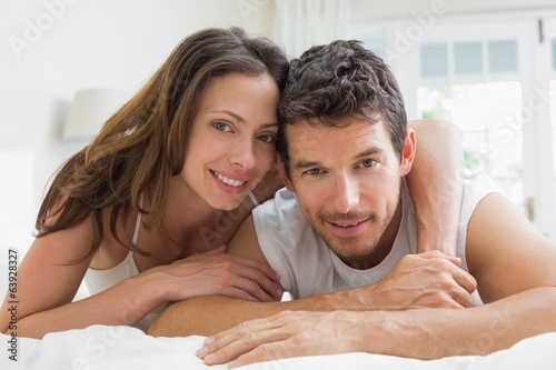 Relaxed young couple lying in bed
