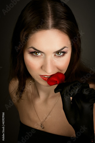 mysterious woman in dark hood with rose leaf