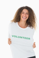 Happy volunteer showing her tshirt to camera