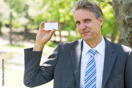 Confident businessman holding business card