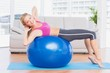 Slim blonde doing sit ups on exercise ball smiling at camera